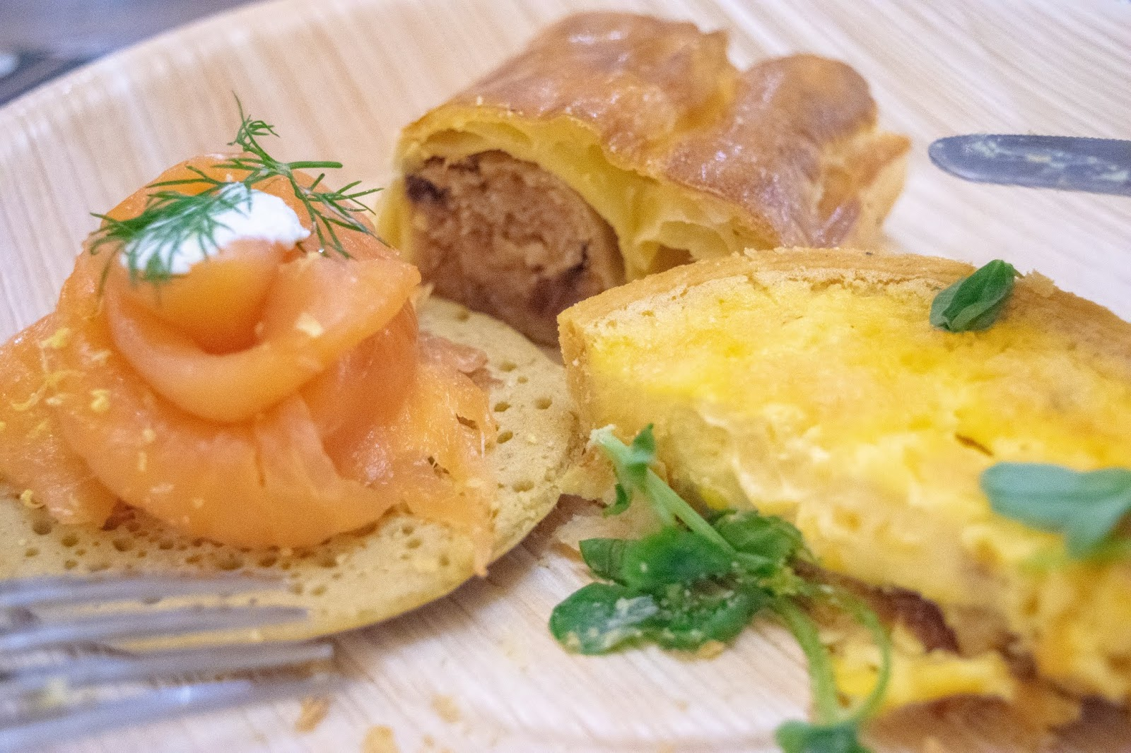 A selection of foods including smoked salmon on a savoury pancake, a cheese tartlet and vegetarian sausage roll.