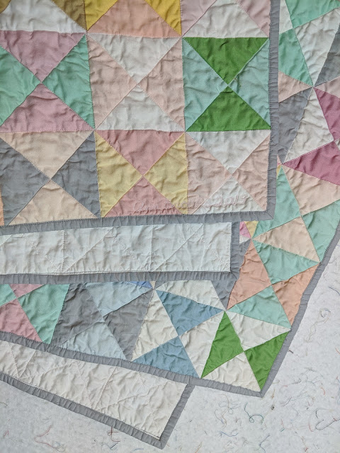 The folded quilt shows the front, back, and grey lawn binding. The stitch-in-the-ditch quilting shows better on the back.