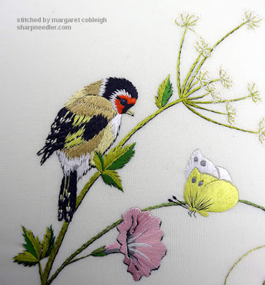 Silk embroidered goldfinch with yellow moth and pink flower