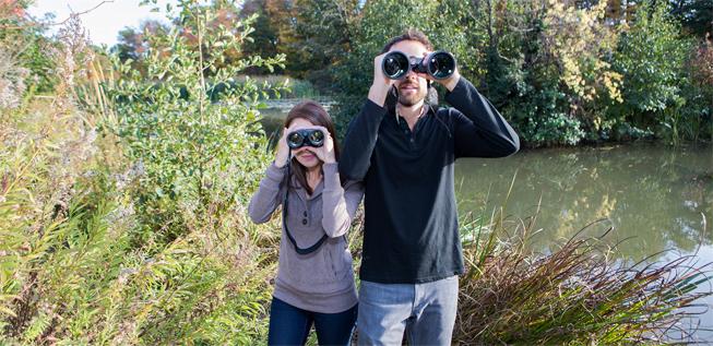 Two Nerds looking through binoculars at birds