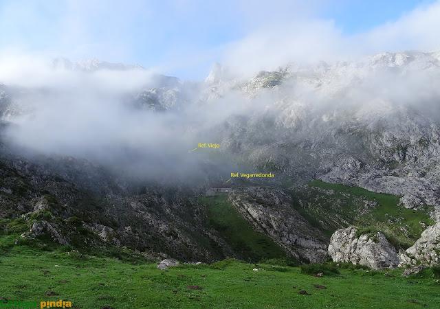 Al fondo los refugios de Vegarredonda entre la niebla