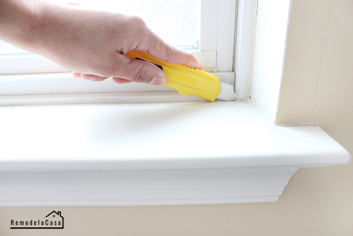 using a utility knife to score the caulking around the window