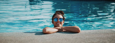 Photo of a woman in the pool with her crossed arms on the edge looking out of the pool. All The Step x Step Learn To Swim Guides
