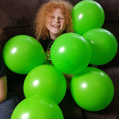 review self sealing Bunch O Balloons party child sitting covered in large balloons