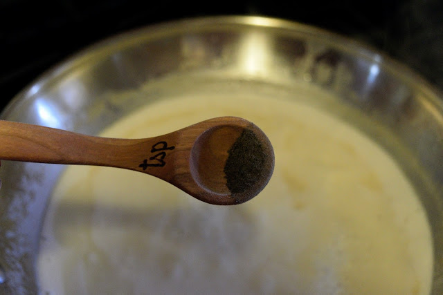 A measuring spoon of pepper over the skillet of Marsala sauce.