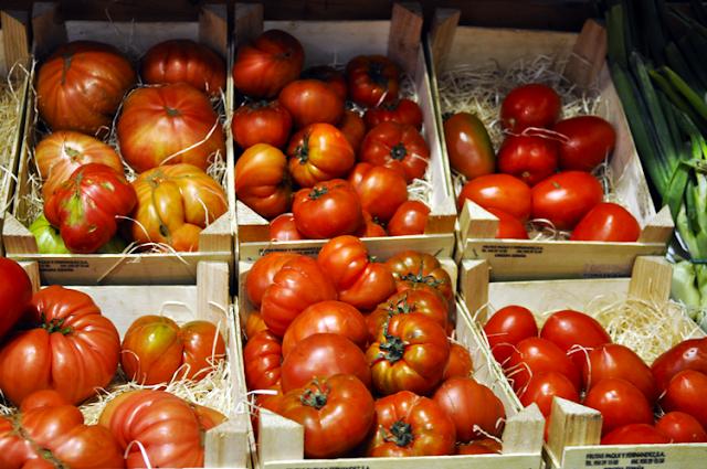 diferentes tomates en cajas de madera