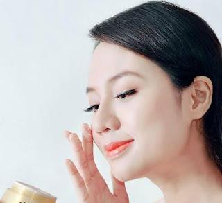 Mulher oriental com pele muito bonita passa creme no rosto