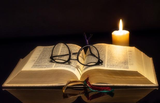 A imagem mostra uma bíblia aberta sobre a mesa, em cima dela vemos um óculos. Ao fundo temos uma vela sob um senário escuro.