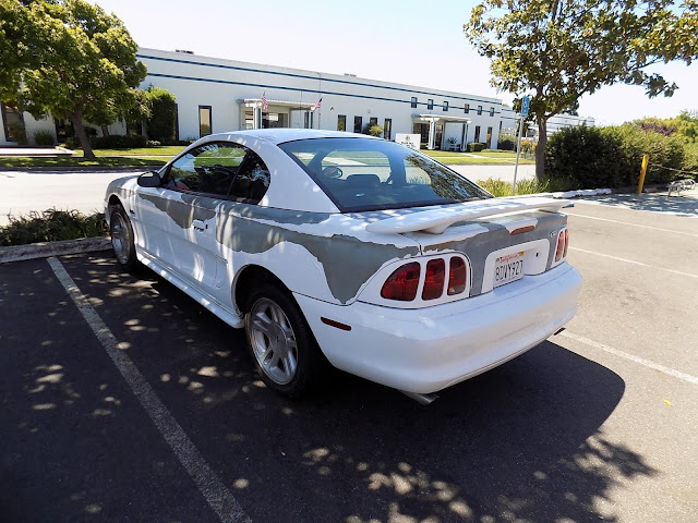 The grey areas are where the original paint had fallen off this Ford Mustang.