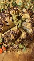 roasted cauliflower head with veggies in cheese sauce