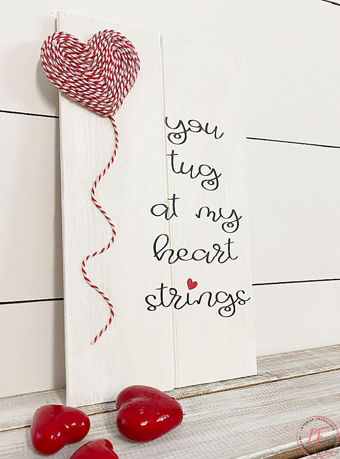 A quick and easy DIY scrap wood sign idea for valentine's day with an adorable heartstring quote that costs next to nothing to make.