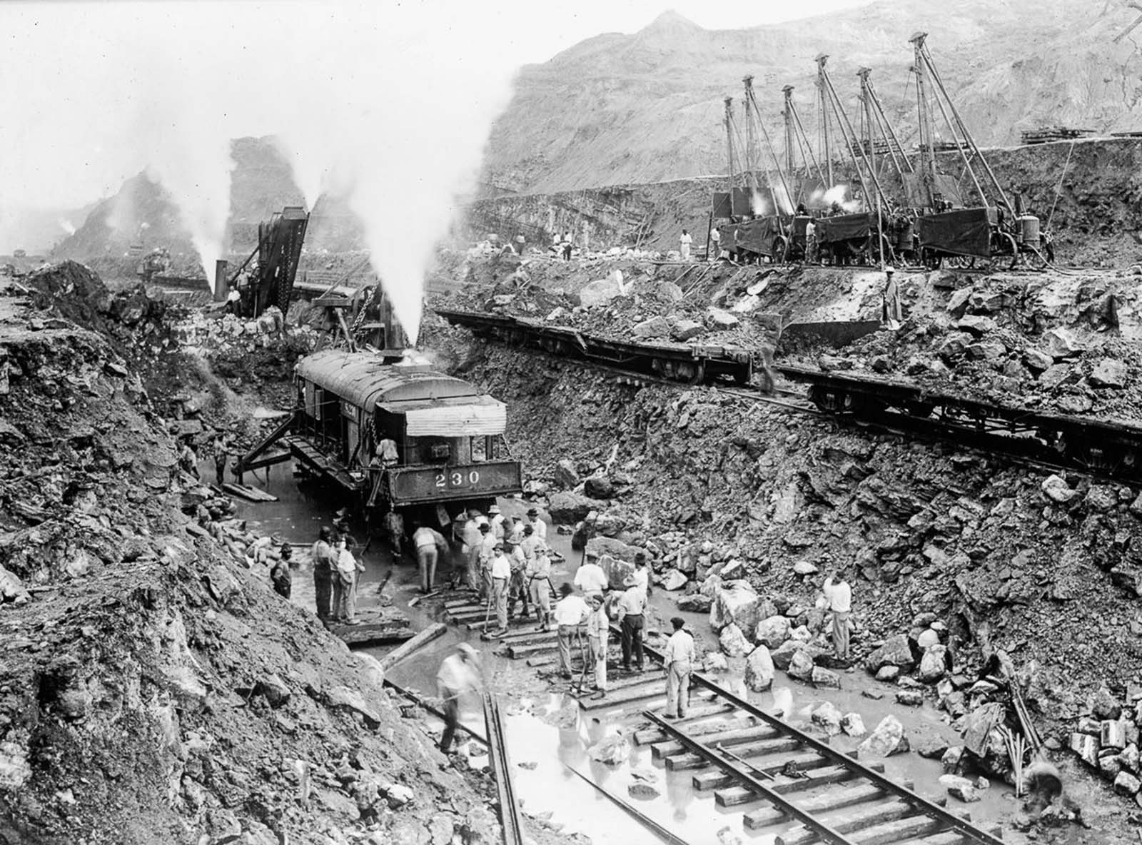 The scale of the work was massive. Six thousand men worked in the cut, drilling holes in which a total of 27,000 t (60,000,000 lb) of dynamite were placed to break up the rock (which was then removed by as many as 160 trains per day).