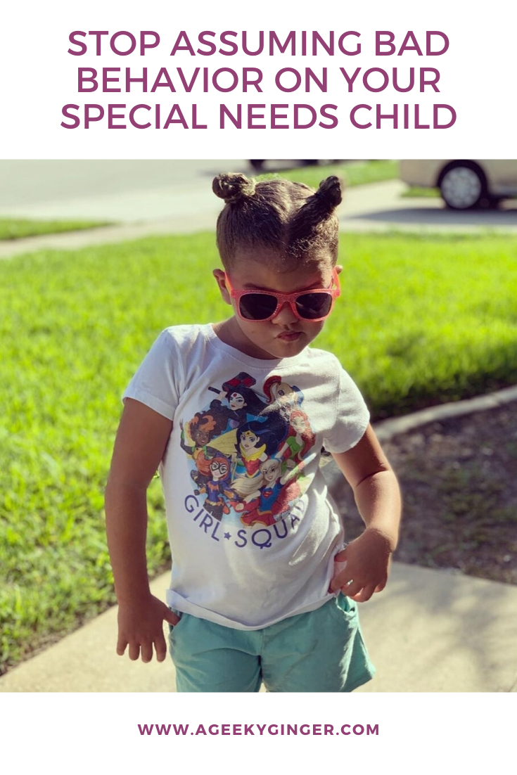 A little girl with space buns, wearing sunglasses and standing in a sassy manner.