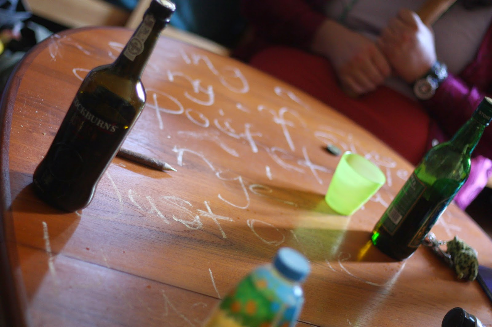 A table with wine bottles, cups and writing on it.