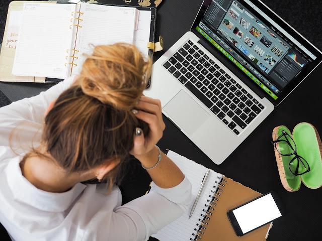 A woman looking stressed at her computer