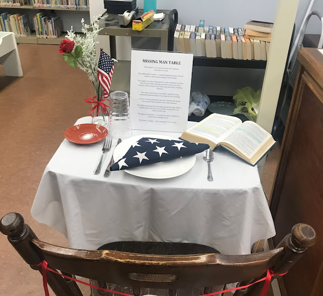 An empty chair is pushed up to a table. The table holds a plate of salt, a folded flag on a plate, an open Bible, a flag in a vase, and Missing Man table guidelines.