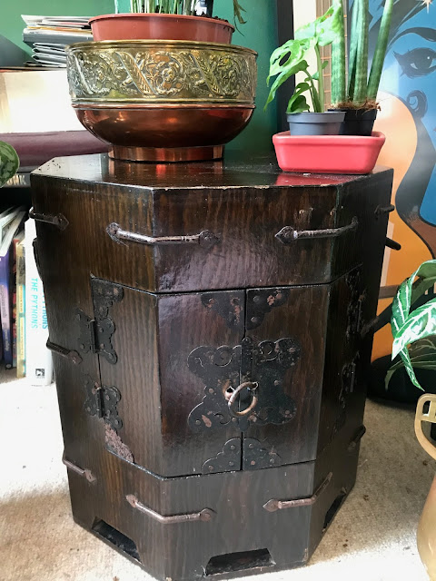 A small octagonal cupboard in dark wood, with a plant in a brass pot on top.