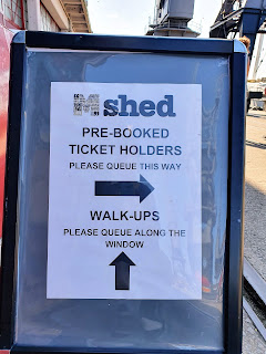 Sign outside a museum saying: Pre-booked tickets holders please queue this way (arrow). Walk-ups please queue along the window (arrow)