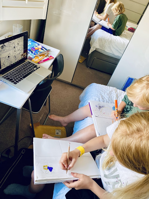 pictures of my daughters drawing a comic with an open laptop in front of them with a zoom session open  showing a newly drawn comic by Neill Cameron