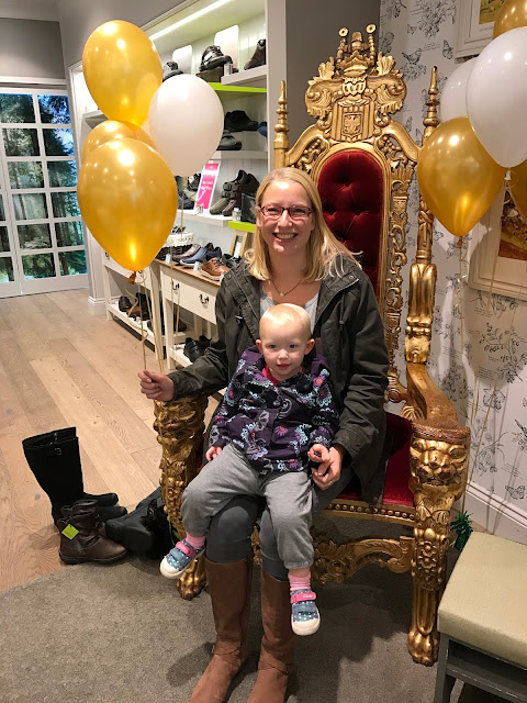 Me sitting on a costume throne, surrounded by balloons and with my toddler on my lap