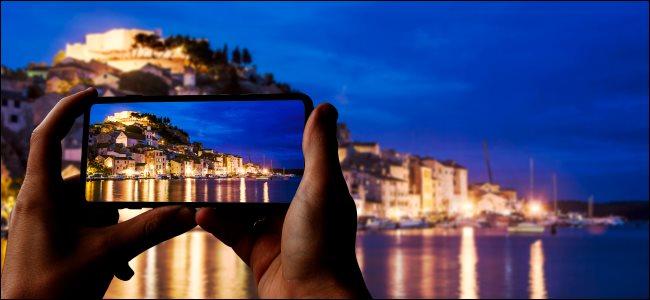 هاتف ذكي يلتقط صورة لمدينة وبحر ليلاً.