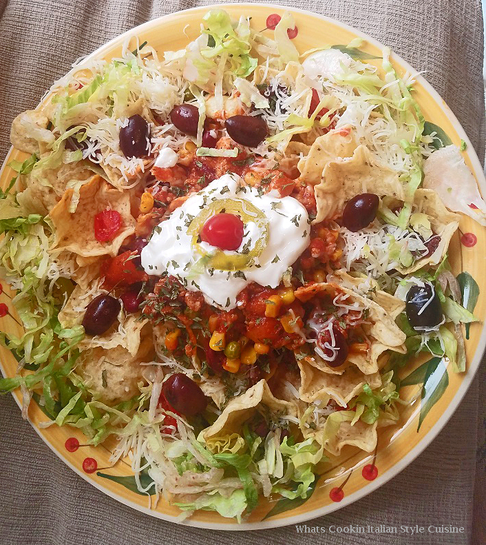 these are Nachos made with a Southwest chili on top, lettuce and olives with jalapeno peppers and sour cream