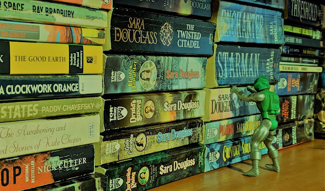A shelf on the bookshelf of fiction with a Dr. Doom plastic figure leaning against some of the books.