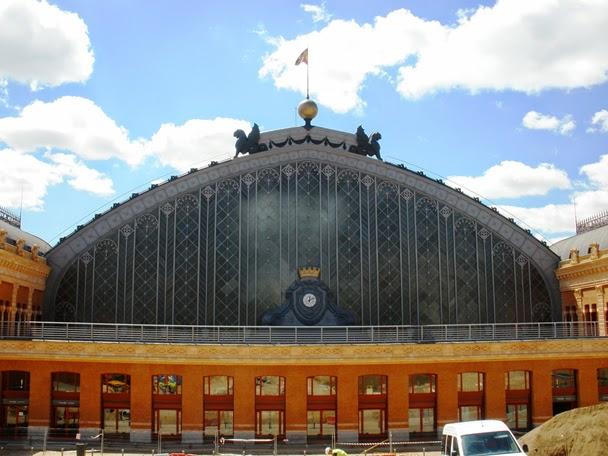 Vista parcial de la fachada de ladrillo, en la que destaca en frontal de la marquesina de trenes, de hierro y vidrio, coronada por dos leones alados.