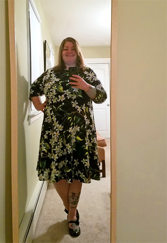 image of me, a short, fat, middle-aged white woman, standing in a full-lenth mirror wearing a black dress with a pattern of white and green flowers and black maryjane shows