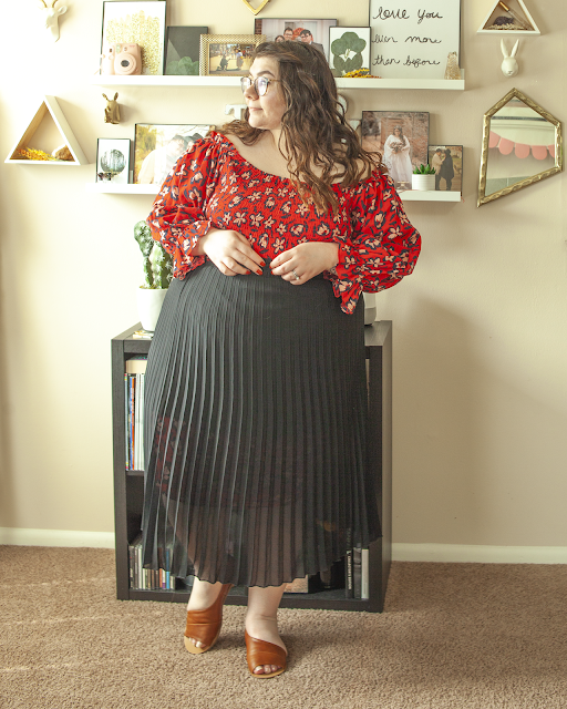 An outfit consisting of a red long sleeve off the shoulder dress with a navy outlined white floral motif, tucked into a black pleated midi skirt and brown d'orsay sandals.