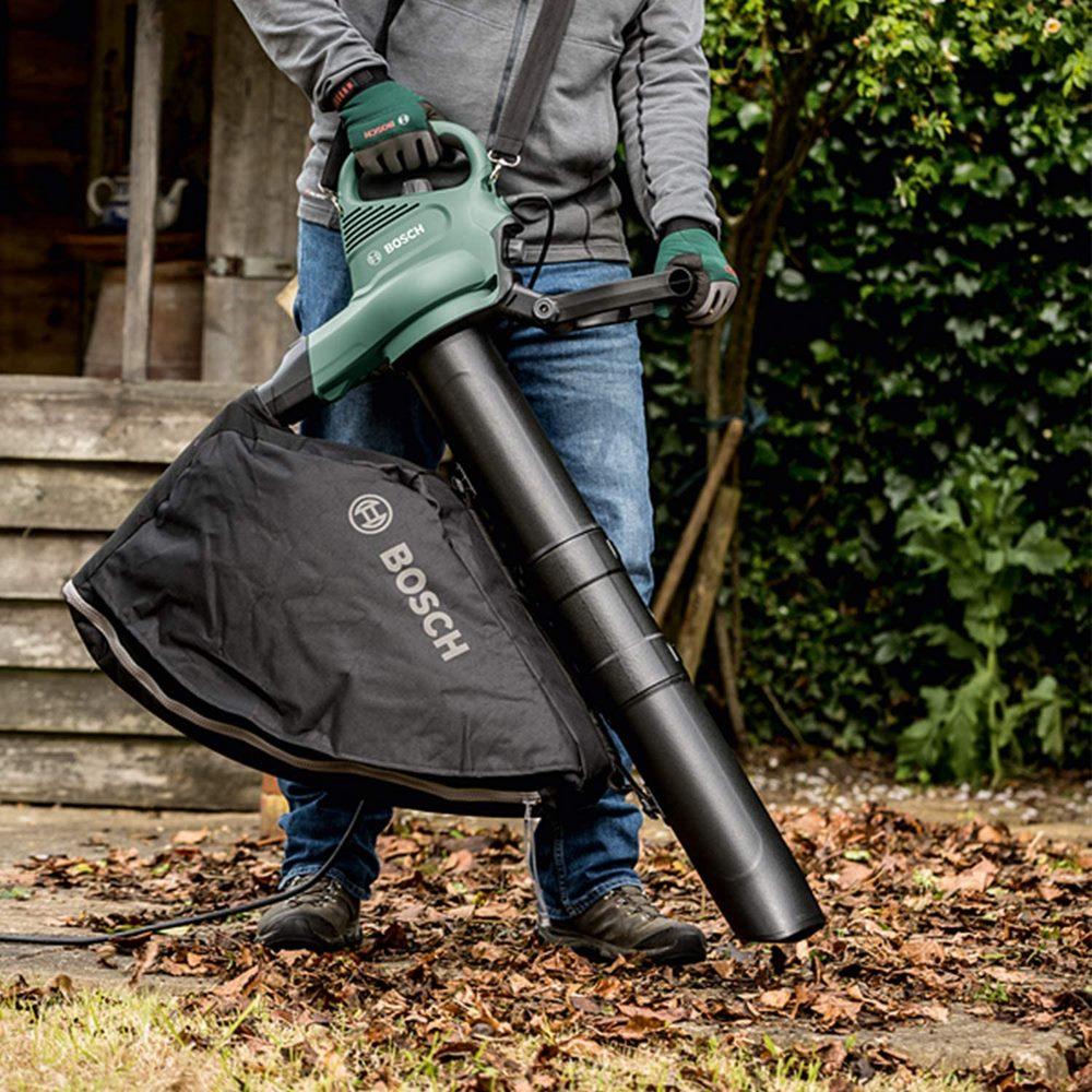 Aspirando hojas de otoño en el jardín con un soplador y aspirador eléctrico