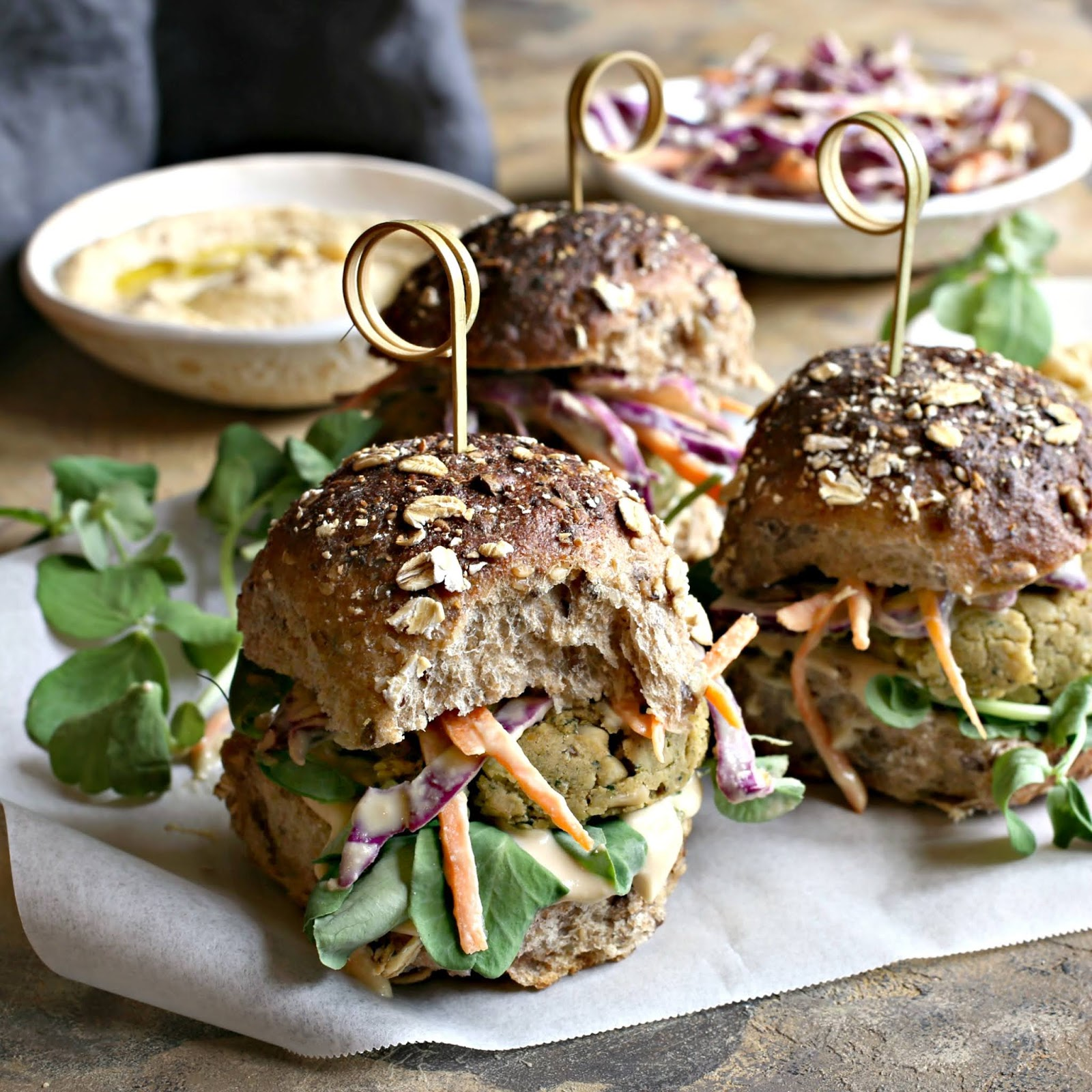 Recipe for baked chickpea and pine nut falafel patties topped with coleslaw in hummus dressing.