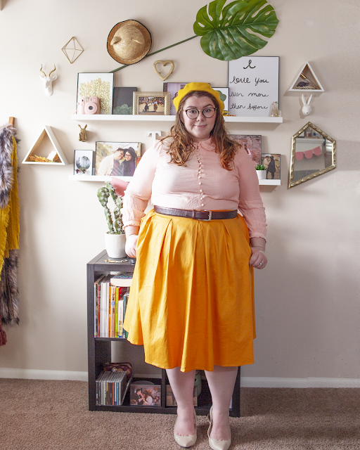 An outfit consisting of a yellow beret, pastel pink peter pan blouse tucked into a yellow midi skirt and beige slingback heels.