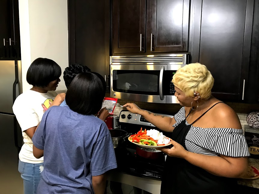 Image: Mom teaching daughters how to prep for cooking