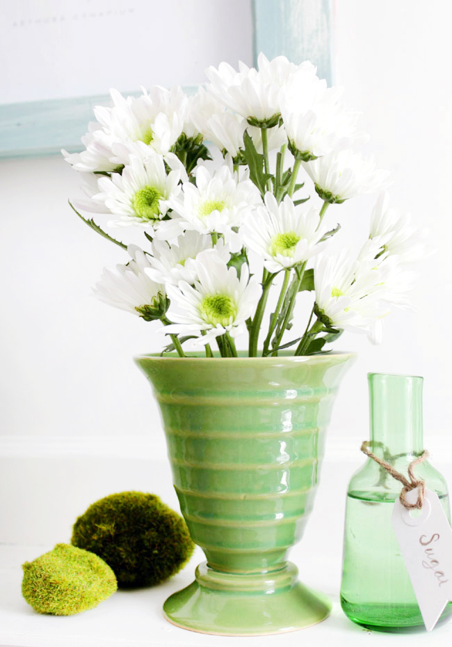 Bouquet of white flowers in green vase on mantel