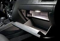 Bir otomobilin açık duran iki katlı ve ışıklı torpido gözü