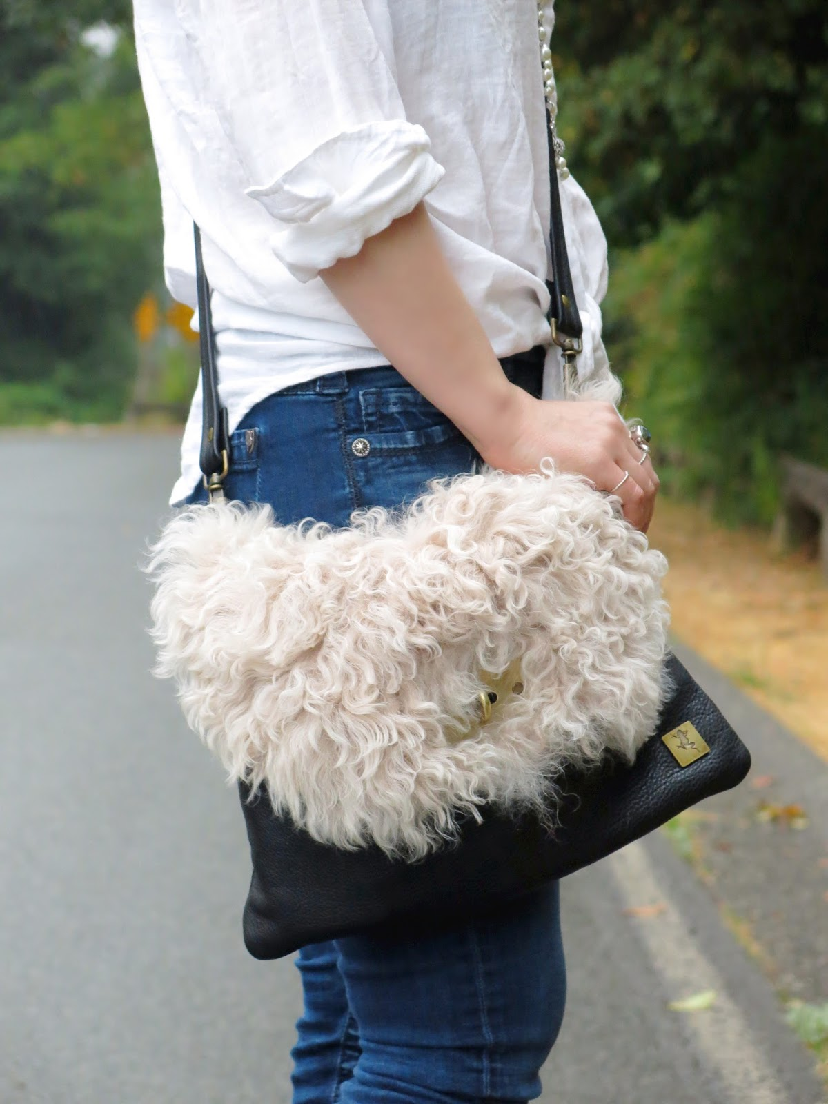 a white shirt, blue denim skinnies, and a furry bag