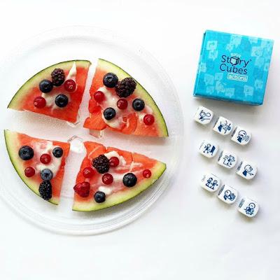 Rodajas de sandía decoradas con yogur y arandanos, junto al juego Story cubes