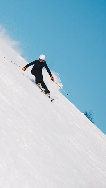 a skiier dressed in black heading down an extremely steep slope