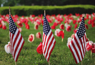 Image of small American Flags placed on a lawn with tulips