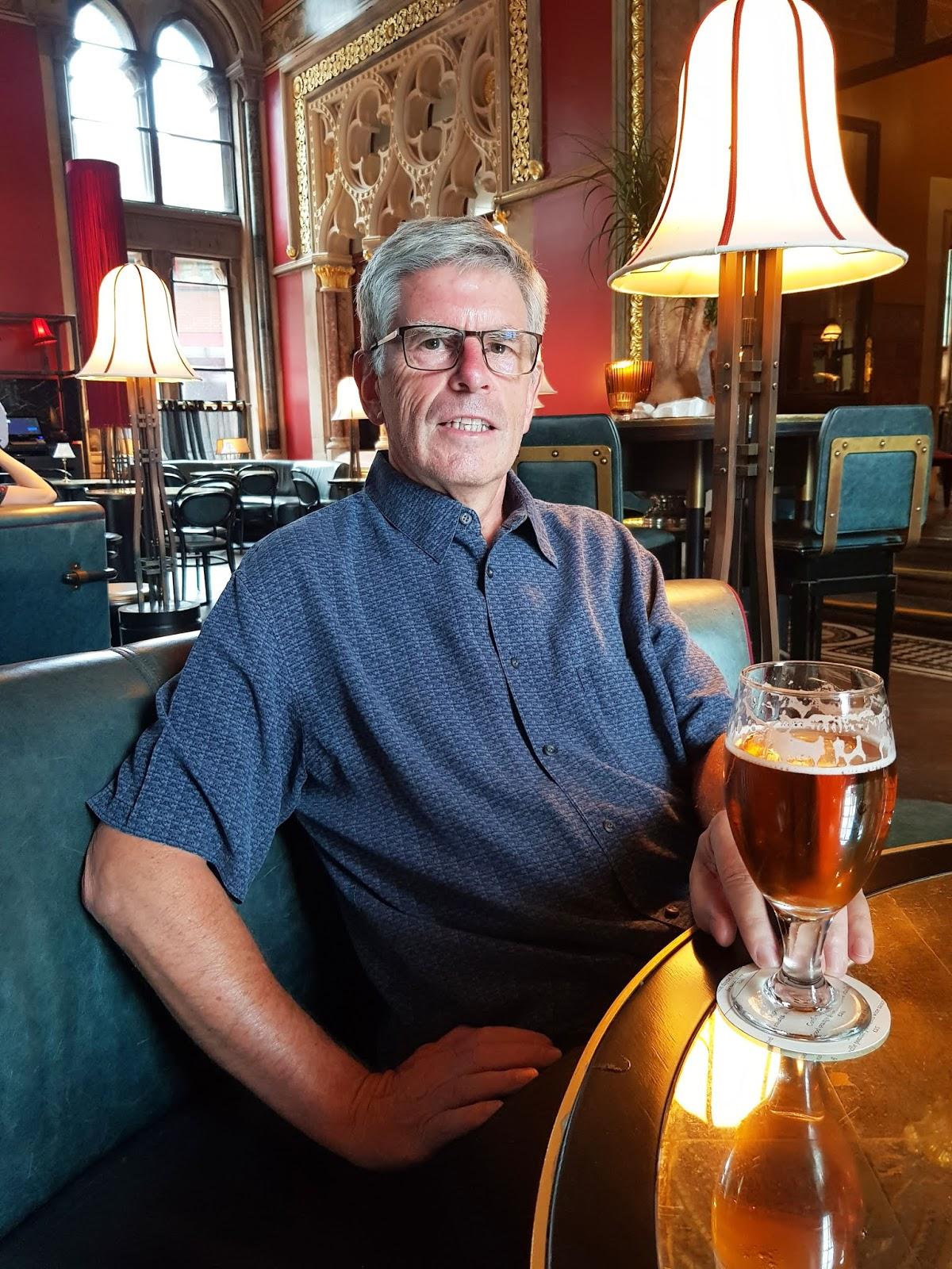 Over 60s man in blue silk shirt enjoying a pint at the Gilbert Scott restaurant in London