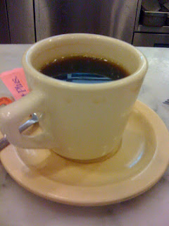 A still photograph of a full cup of black coffee (with a torn sweet and low on the saucer)