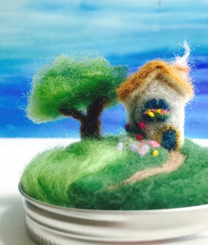 Felted Fairy Tale.  Buat miniatur bukit, rumah, dan pohon, lengkap dengan bunga-bunganya di atas tutup toples. Bahan yang digunakan adalah kain felt, benang wool, dan lem. Pajang dalam keadaan tertutup toples kaca supaya tidak mudah kotor.