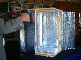 homem terminando a colocação da lamina térmica na estufa de madeira