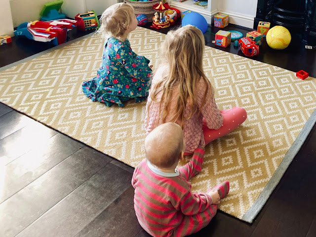 My children (2 girls and a Baby Boy) sitting on a rug staring in front of them at a TV screen which isn't visible for a cosmic yoga session which was their PE lesson as part of coronavirus homeschooling