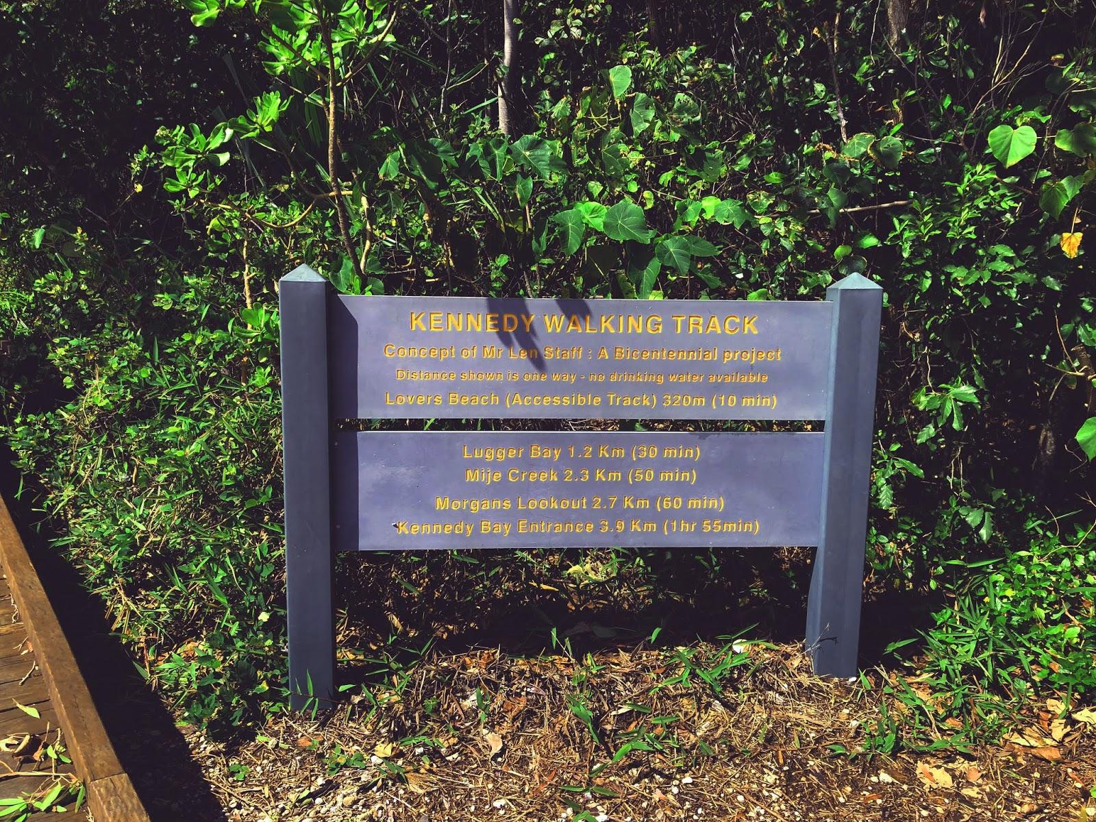 Zdjęcie drewnianej tablicy w australijskim miasteczku Mission Beach, która informuje o tym, że znajdujemy się na początku drewnianej ścieżki Kennedy Walking Track, która znajduje się tuż obok Morza Koralowego.