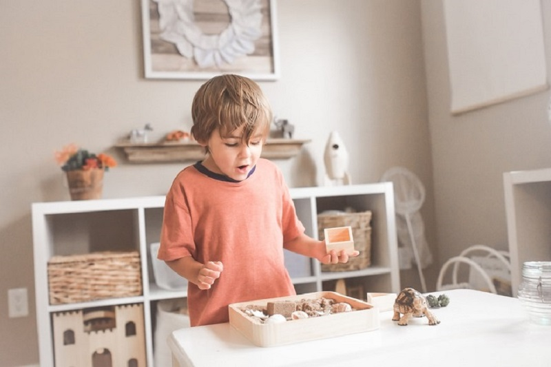 little boy playing with wooden loose parts tray