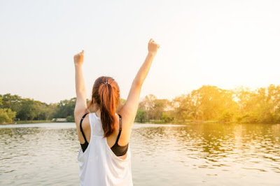 Be happy: woman holds both arms in the air