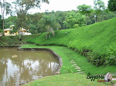 Pisadeiras de pedra no jardim, tipo pedra São Tomé cacão. Pisadeira de pedra em volta da construção do lago com os muros de pedra e no talude o gramado com grama amendoim em sítio em Nazaré Paulista-SP.