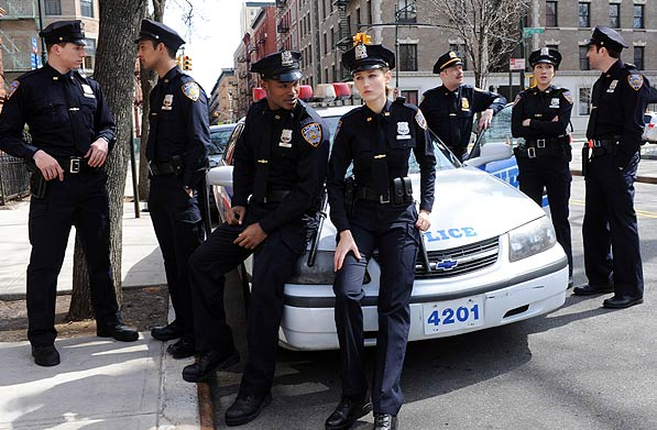 NYC 22 Cast Members all in police uniforms gather around a police car